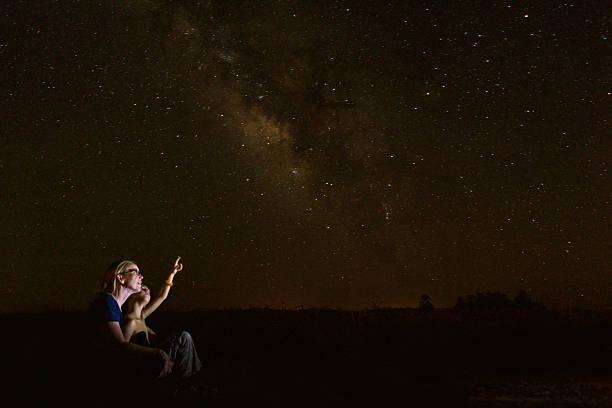mère admirer les étoiles avec son jeune fils pendant qu'il étudie, le constellations - astronomie photos et images de collection