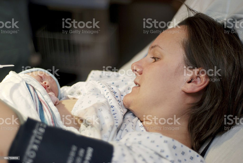 Mother still on the hospital bed after her baby was born royalty-free stock photo
