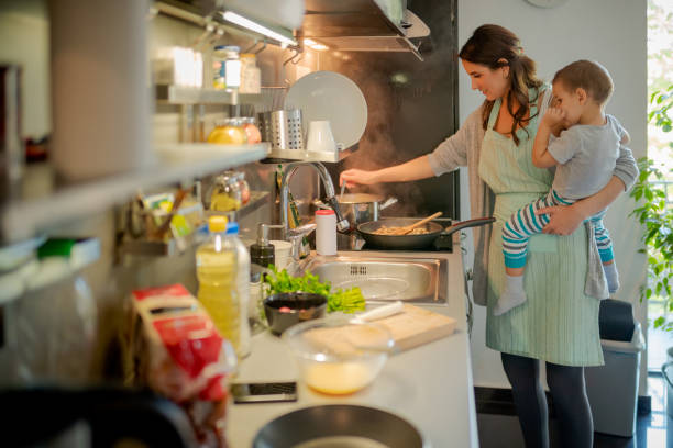 Mother stirring food with the toddler on hip stock photo