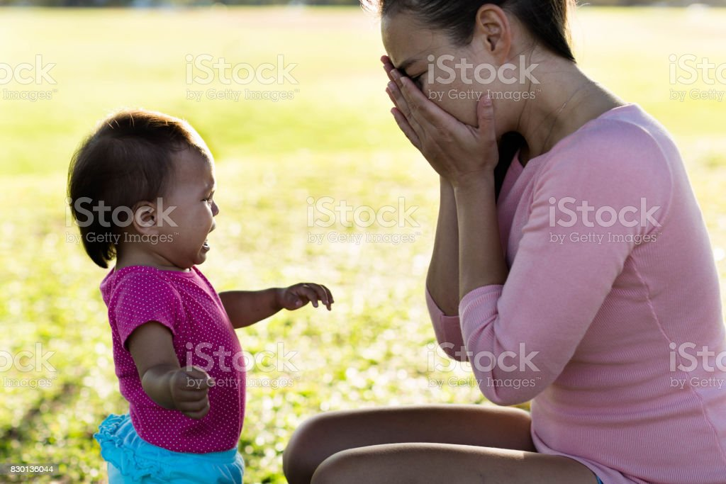 Mother stressed out while baby is crying stock photo