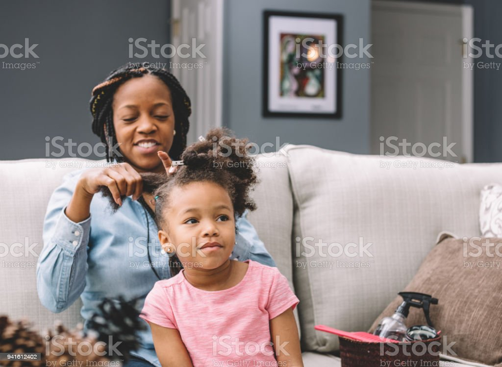 mother styling daugher's hair stock photo