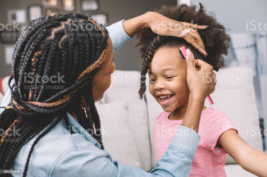 mother styling daughter's curly hair stock photo