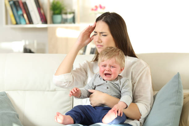 Mother suffering and baby crying desperately stock photo