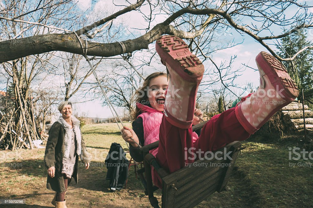 Mother swaying her daughter on a swing stock photo