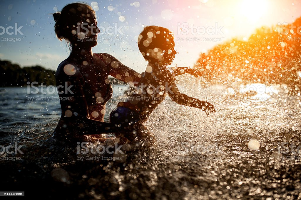 mother swim with baby in blue water at sunset; stock photo