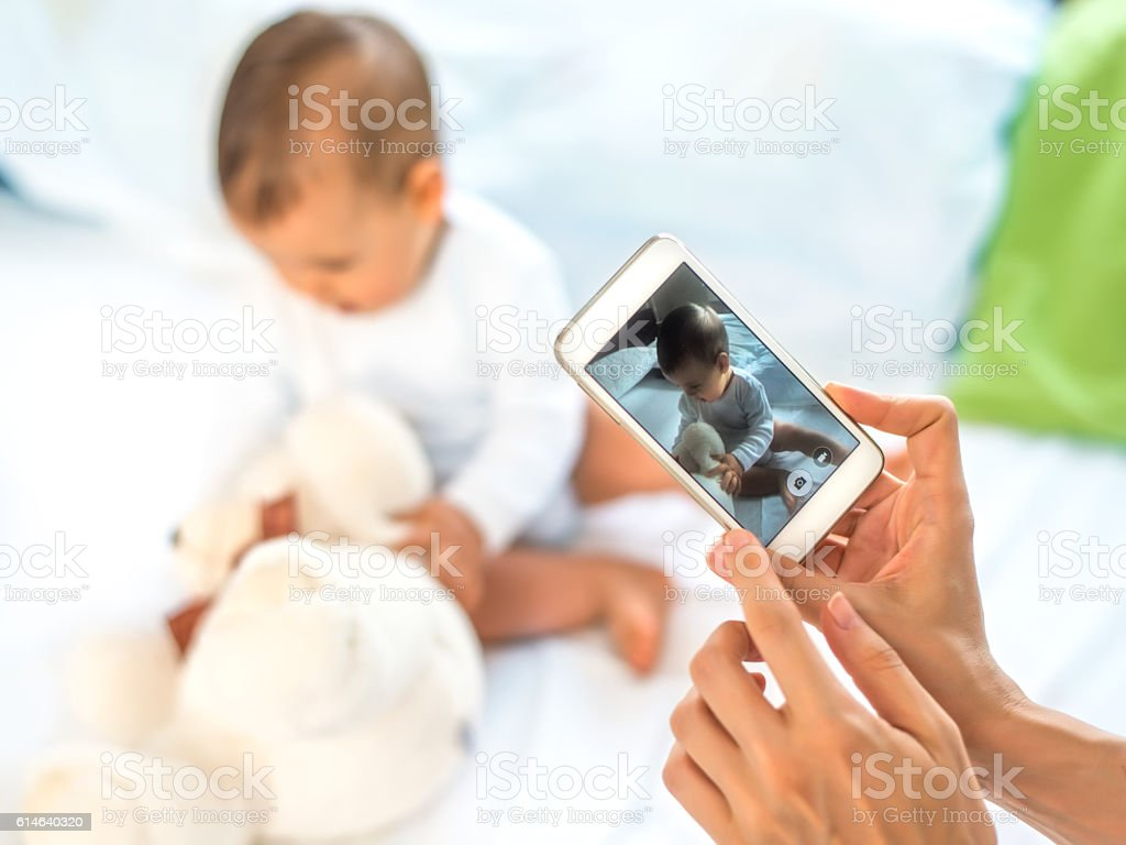 Mother take a photo of her baby stock photo