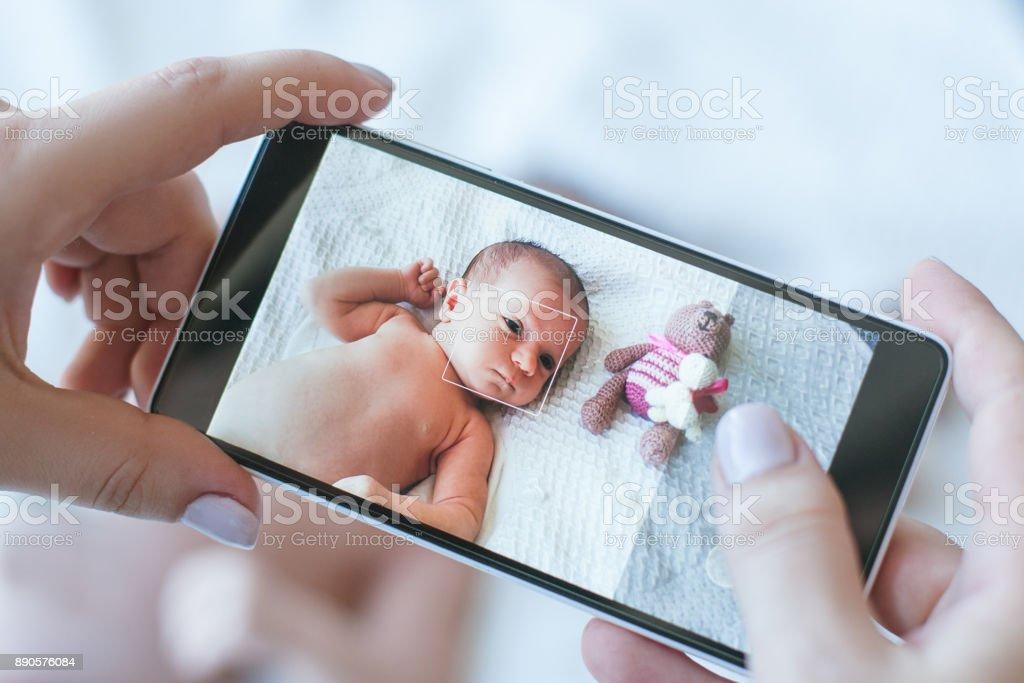 madre toma una foto de smartphone de su bebé recién nacido - foto de stock
