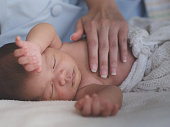 istock Mother take care of Asian female newborn baby lying in bed and sunlight in the morning. Cute little girl three weeks old. Healthcare, love, relationship concept 1138322732