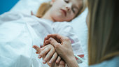 istock Mother Takes and Holds Hand of Her Sick Little Girl who Is Sleeping in the Hospital Bed. Sad and Hopeful Emotional Moment in Pediatric Ward. 1038800000