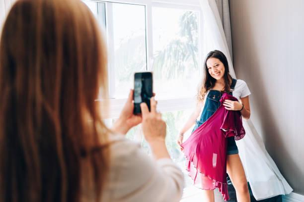 mutter fotografiert mit smartphone ihrer tochter mit kleid - lila teenschlafzimmer stock-fotos und bilder