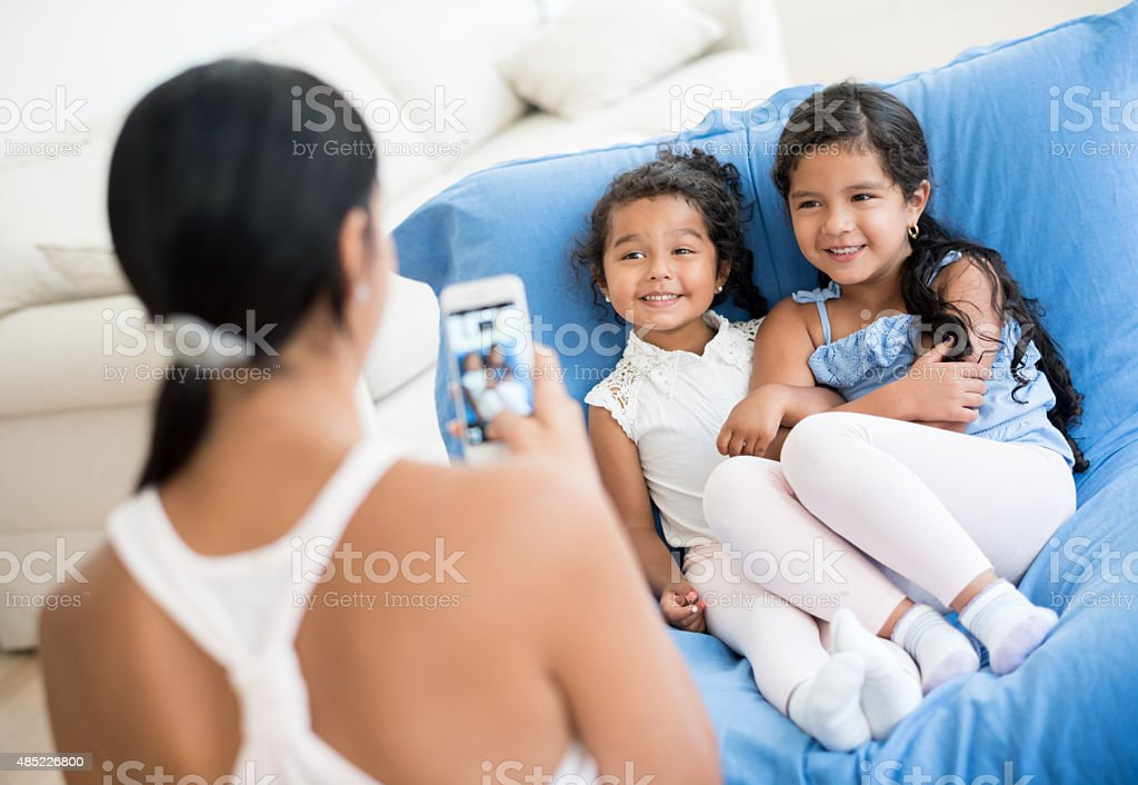 Mother taking a picture to her daughters stock photo