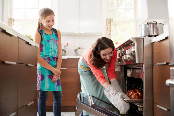 Mother taking bread out of the oven while daughter watches Mother taking bread out of the oven while daughter watches baking bread stock pictures, royalty-free photos & images