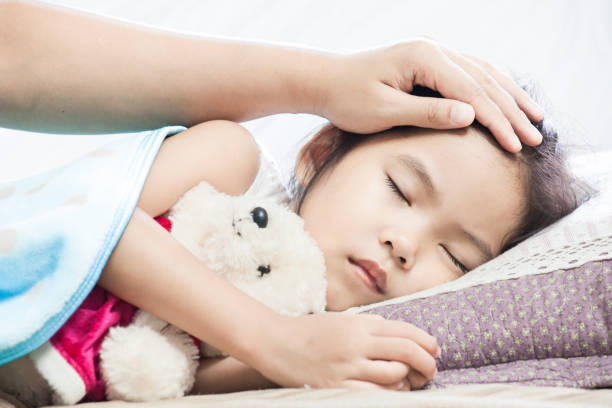 Mother taking care asian child girl while she sleeping in the bed stock photo