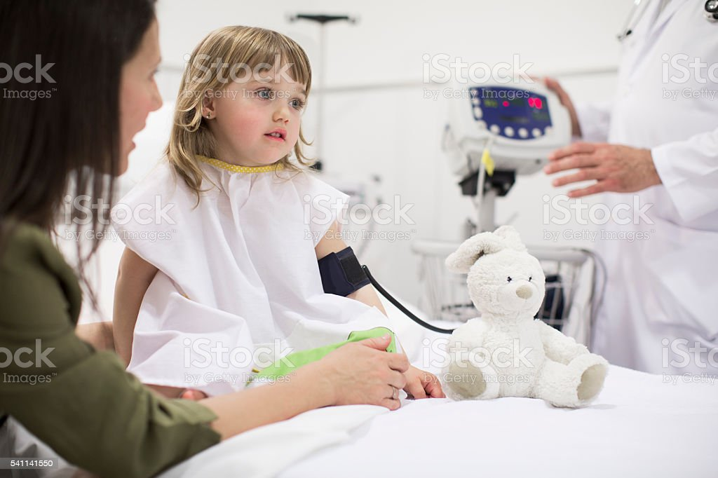 Mother taking care of her daughter in the hospital stock photo