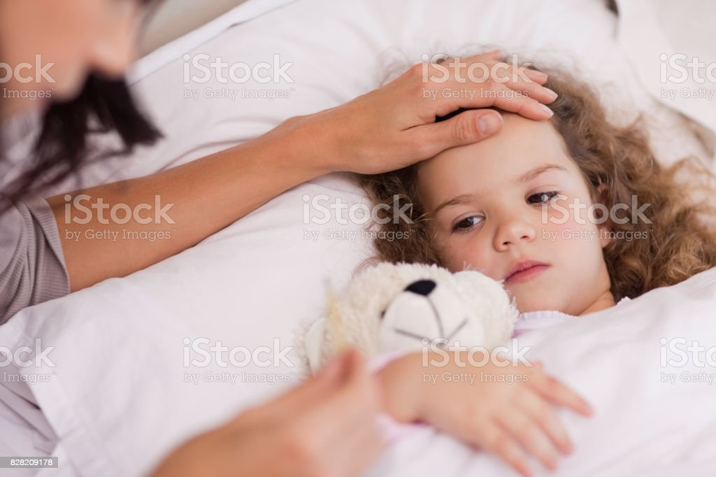 Mother taking care of her ill daughter stock photo