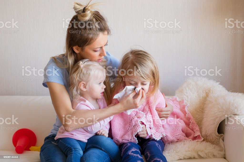 Mother taking care of her sick child stock photo