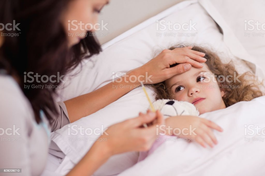 Mother taking care of her sick daughter stock photo