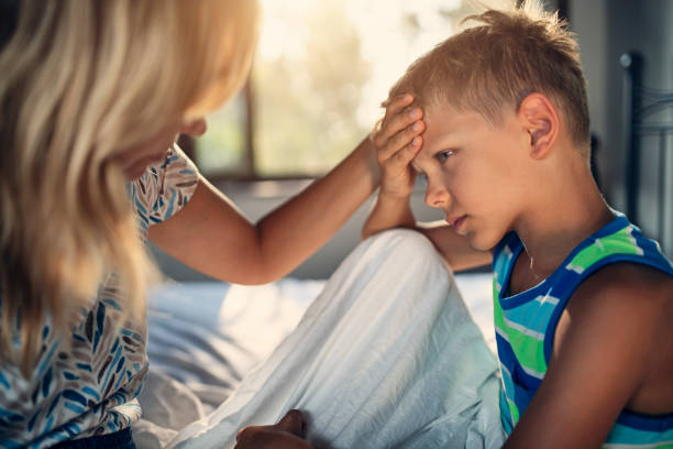 Mutter kümmert sich um kleinen Jungen mit Kopfschmerzen – Foto