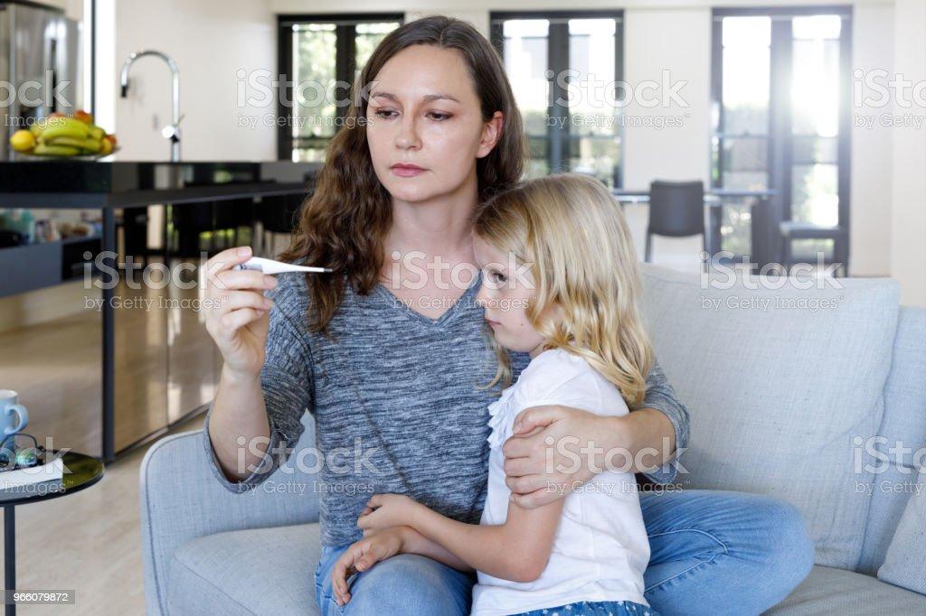 Mamma tar barnets temperatur med termometer - Royaltyfri 6-7 år Bildbanksbilder