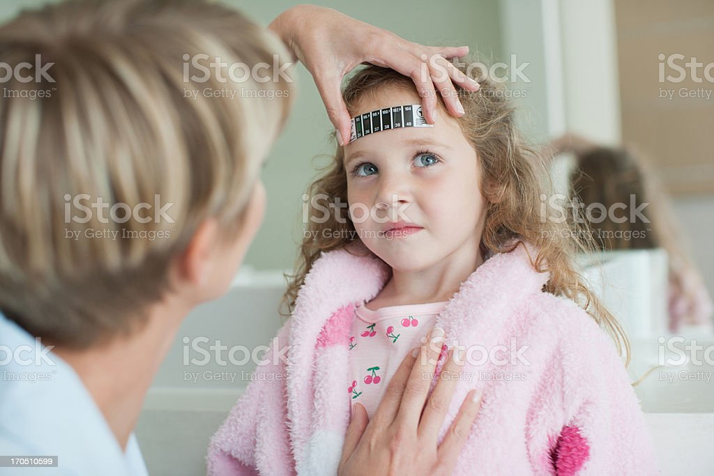 Mother taking daughter's temperature royalty-free stock photo