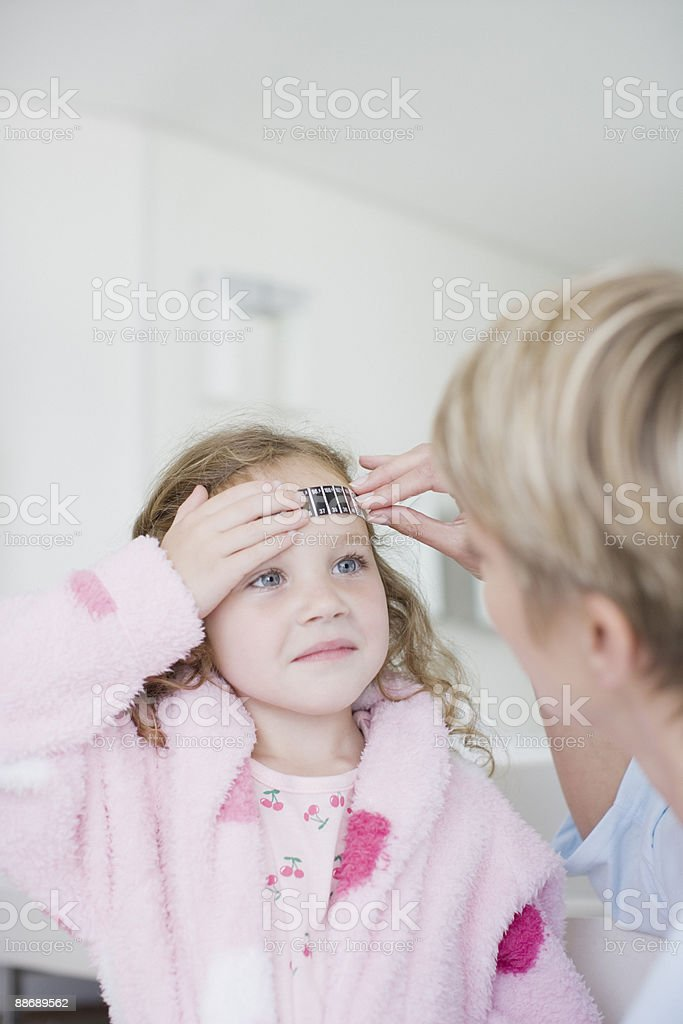 Mother taking daughters temperature royalty-free stock photo