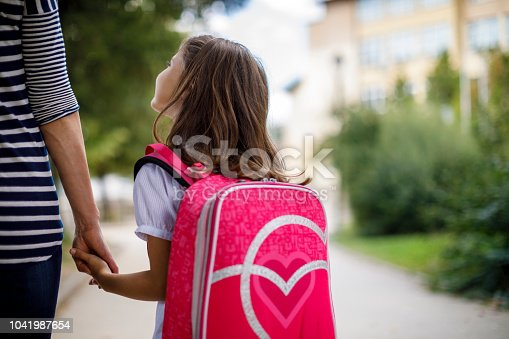 Mother taking her daughter to school