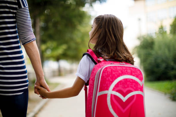Mother taking her daughter to school stock photo