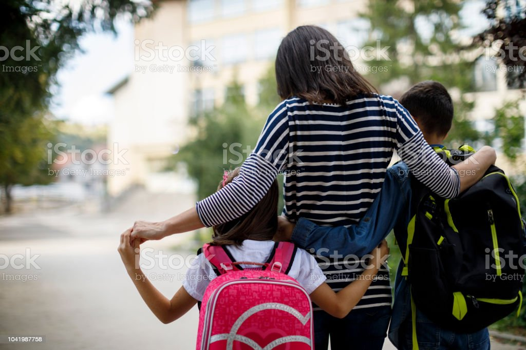 Mother taking kids to school stock photo