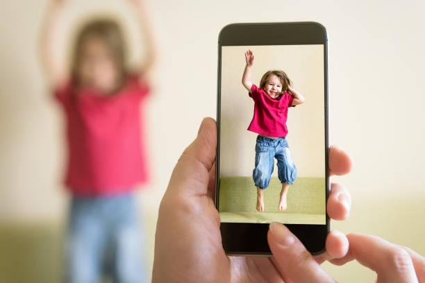 mutter fotografiert gesprengtes baby mädchen mit ihrem handy - lustige babybilder stock-fotos und bilder