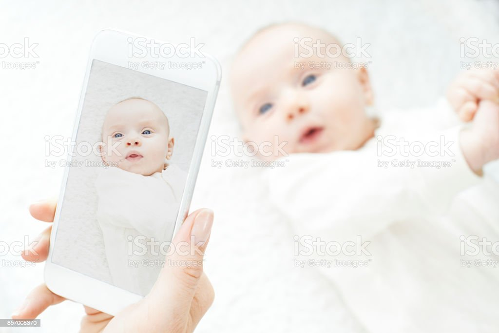 Mother Taking Picture Of Baby Girl On Mobile Phone stock photo