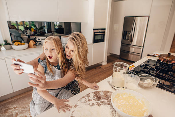 Mother taking selfie with her daughter in kitchen stock photo