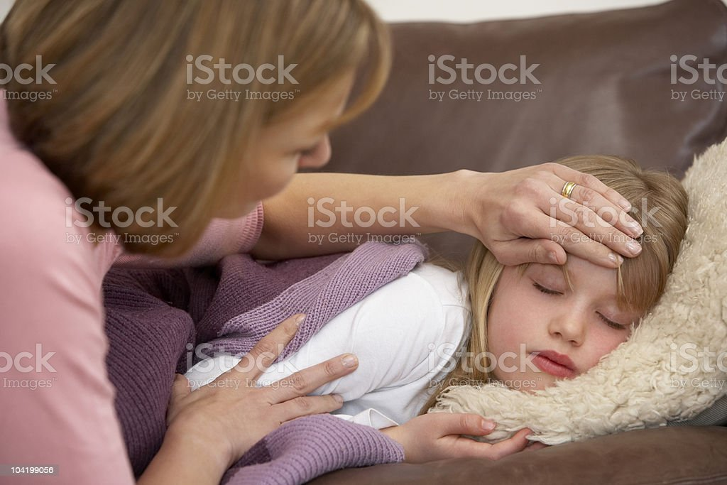 Mother taking temperature of sick daughter at home stock photo