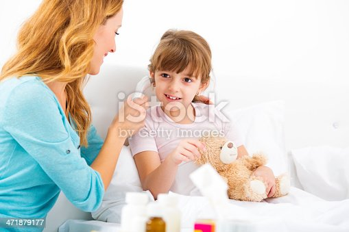 Cheerful mother taking temperature to her sick child, cute little girl. Daughter sitting on bed. Mother using digital ear thermometer.
