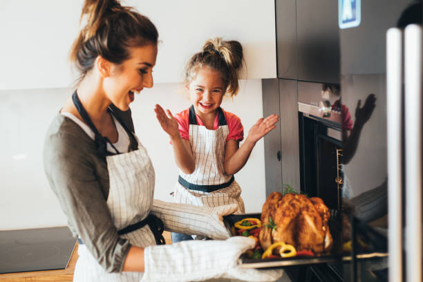 mother taking the dinner out of the oven - kids cooking stock photos and pictures