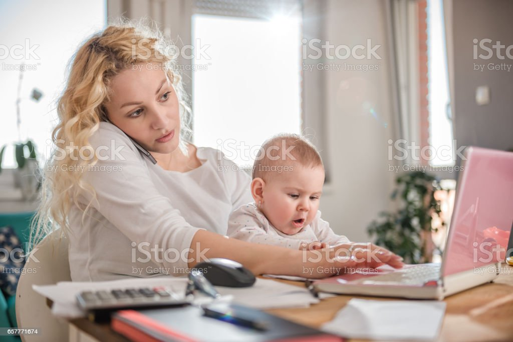 Mother talking on smart phone at home office stock photo