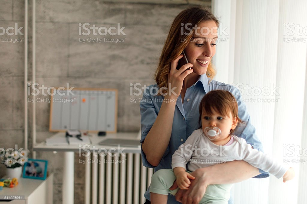 Mother Talking On The Phone And Holding Her Baby stock photo