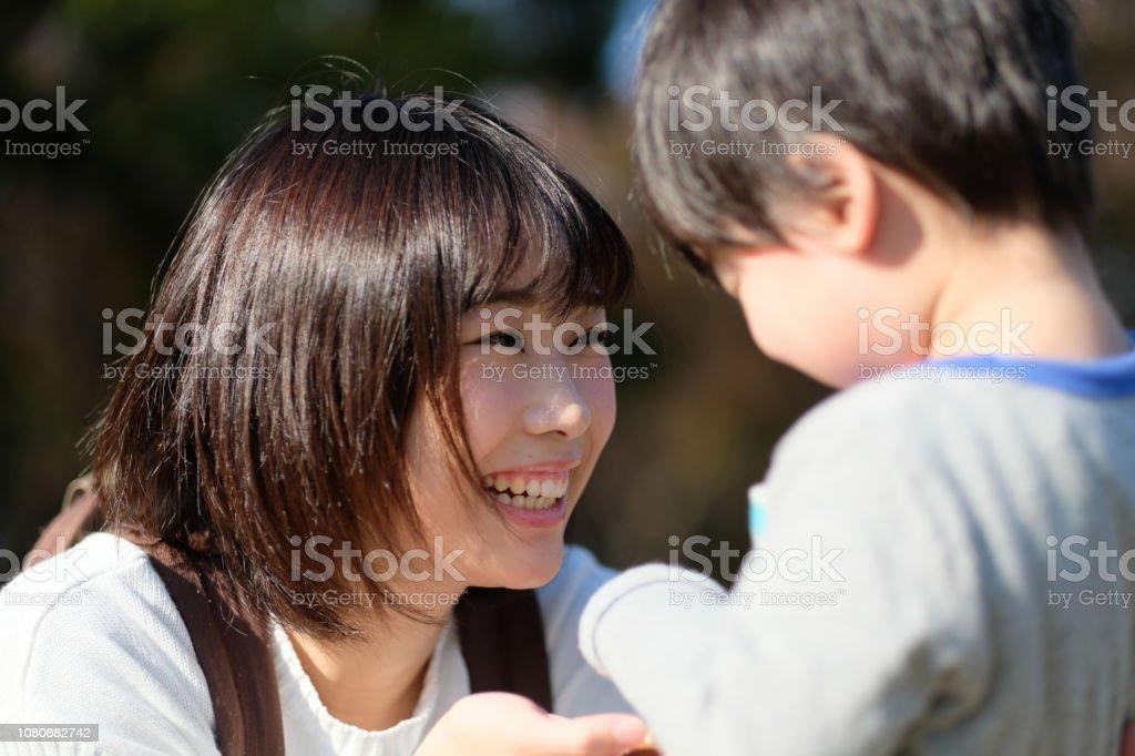 公園で子供に話しかける母 ストックフォト