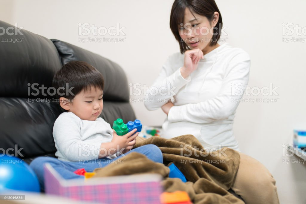 Mother talking to child on sofa stock photo