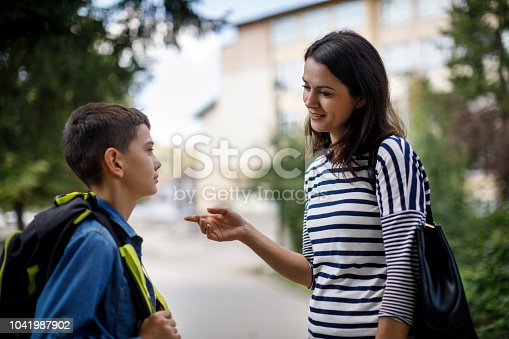 istock Mother talking to son in front of the school 1041987902