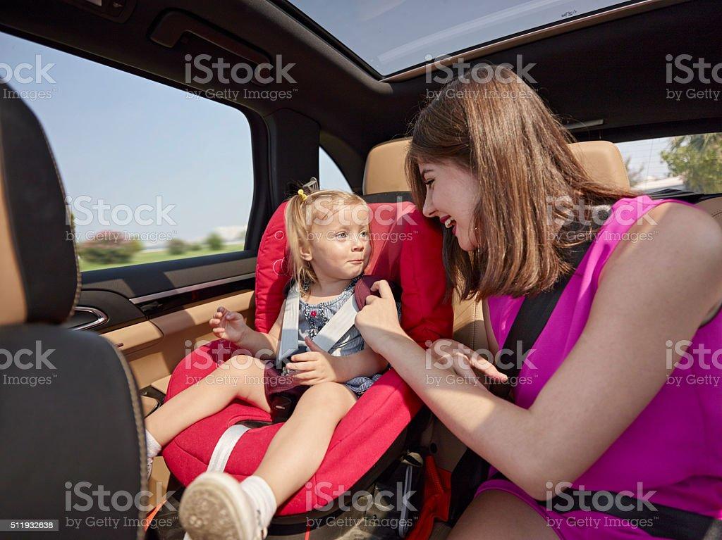 Femme parlant avec sa fille dans un siège de voiture - Photo