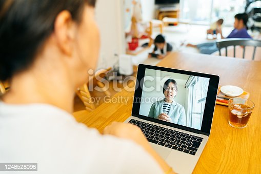 A mother is talking with a mental health professional via web conference at home while her children are playing in the background.