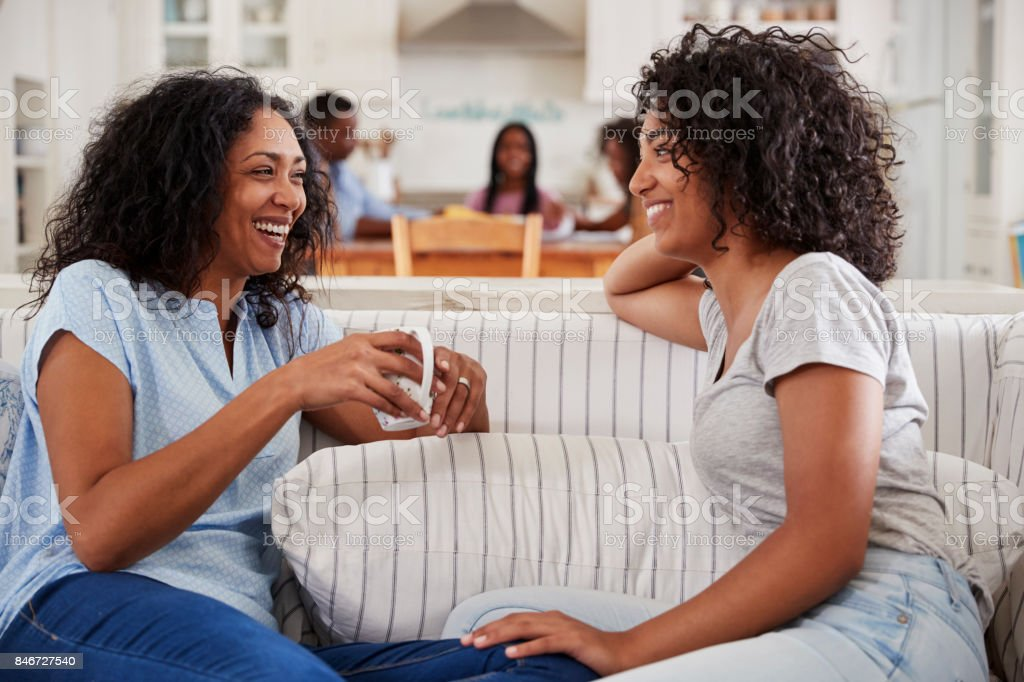 Mother Talking With Teenage Daughter On Sofa stock photo