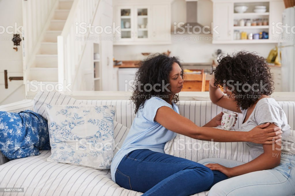 Mother Talking With Unhappy Teenage Daughter On Sofa stock photo