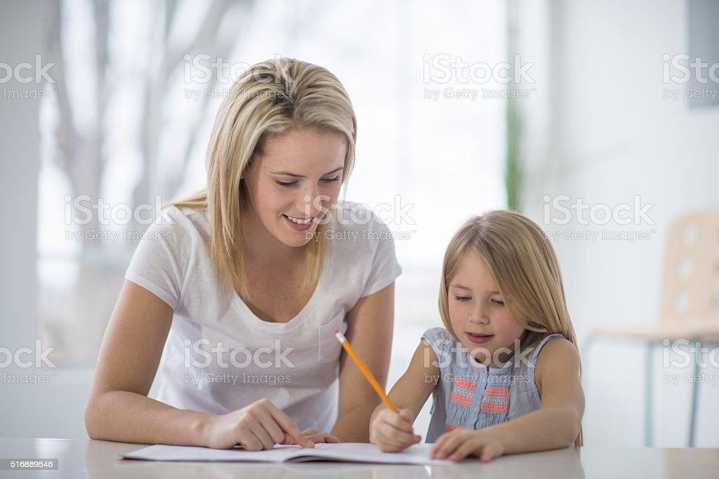 Mother Teacher Her Daughter at Home stock photo