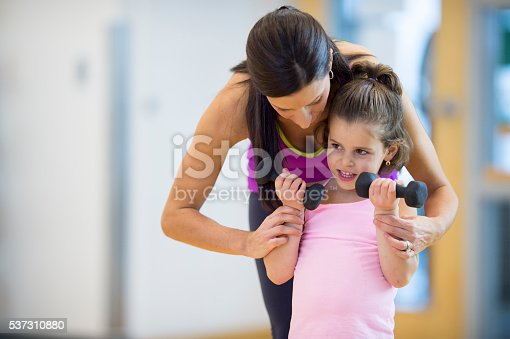 A mother is teaching her daughter how to lift weights at the gym.