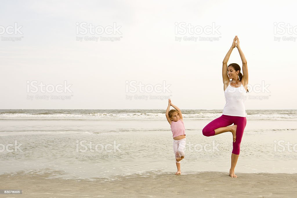 Mother teaches daughter yoga on beach foto stock royalty-free