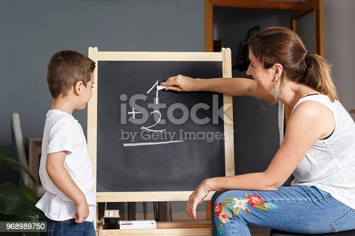 istock Mother teaches her son math at home with a blackboard 968989750