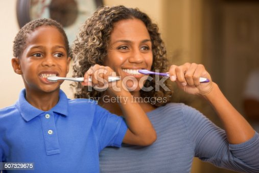 istock Mother teaches son how to properly brush his teeth. Bathroom. 507329675