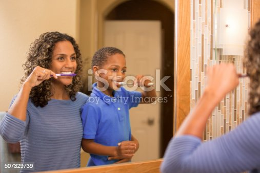 istock Mother teaches son how to properly brush his teeth. Bathroom. 507329739