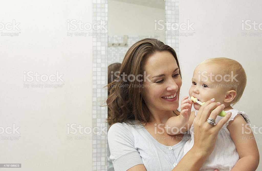 Mother teaching baby how to brush teeth with toothbrush stock photo